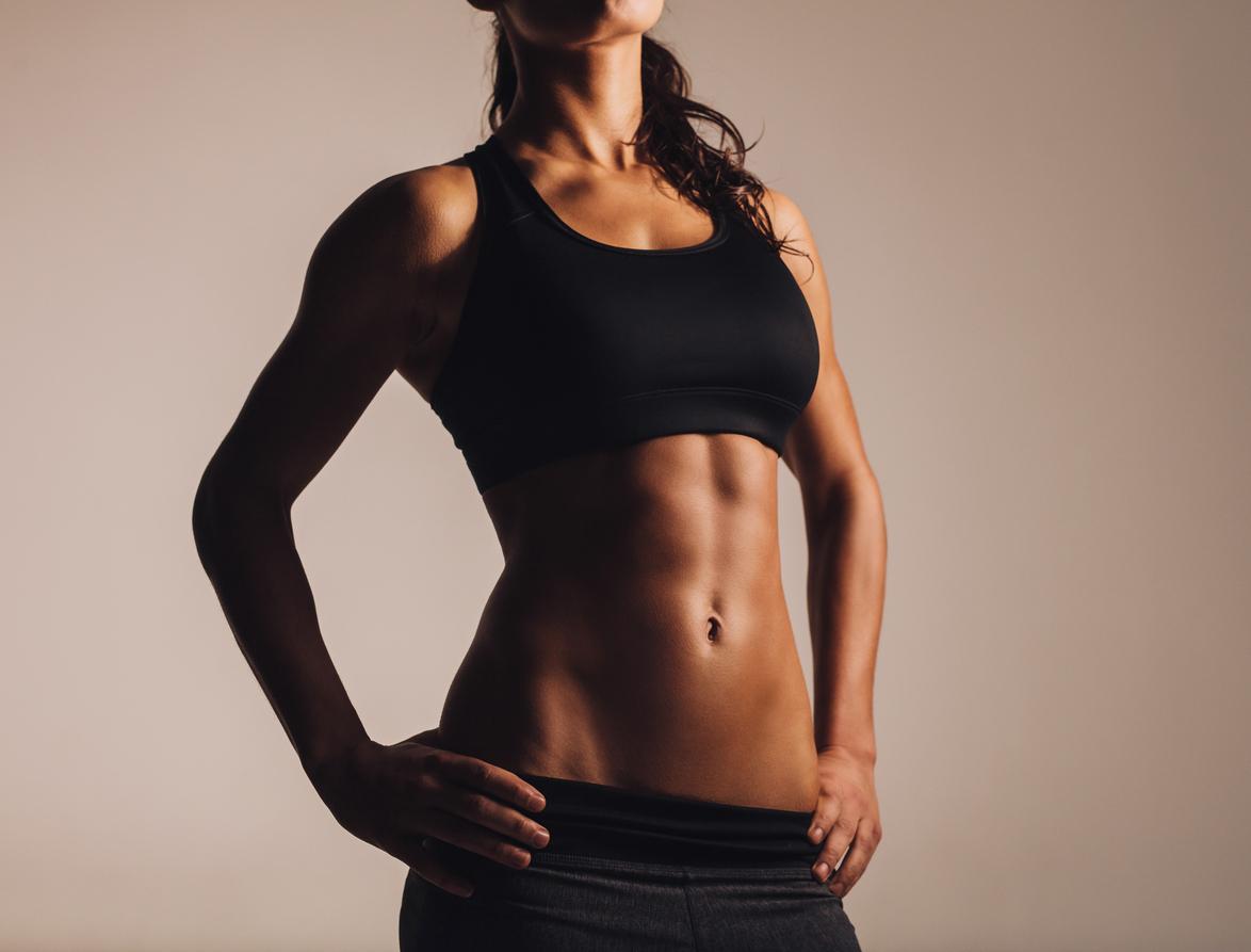 Muscular young woman in sportswear