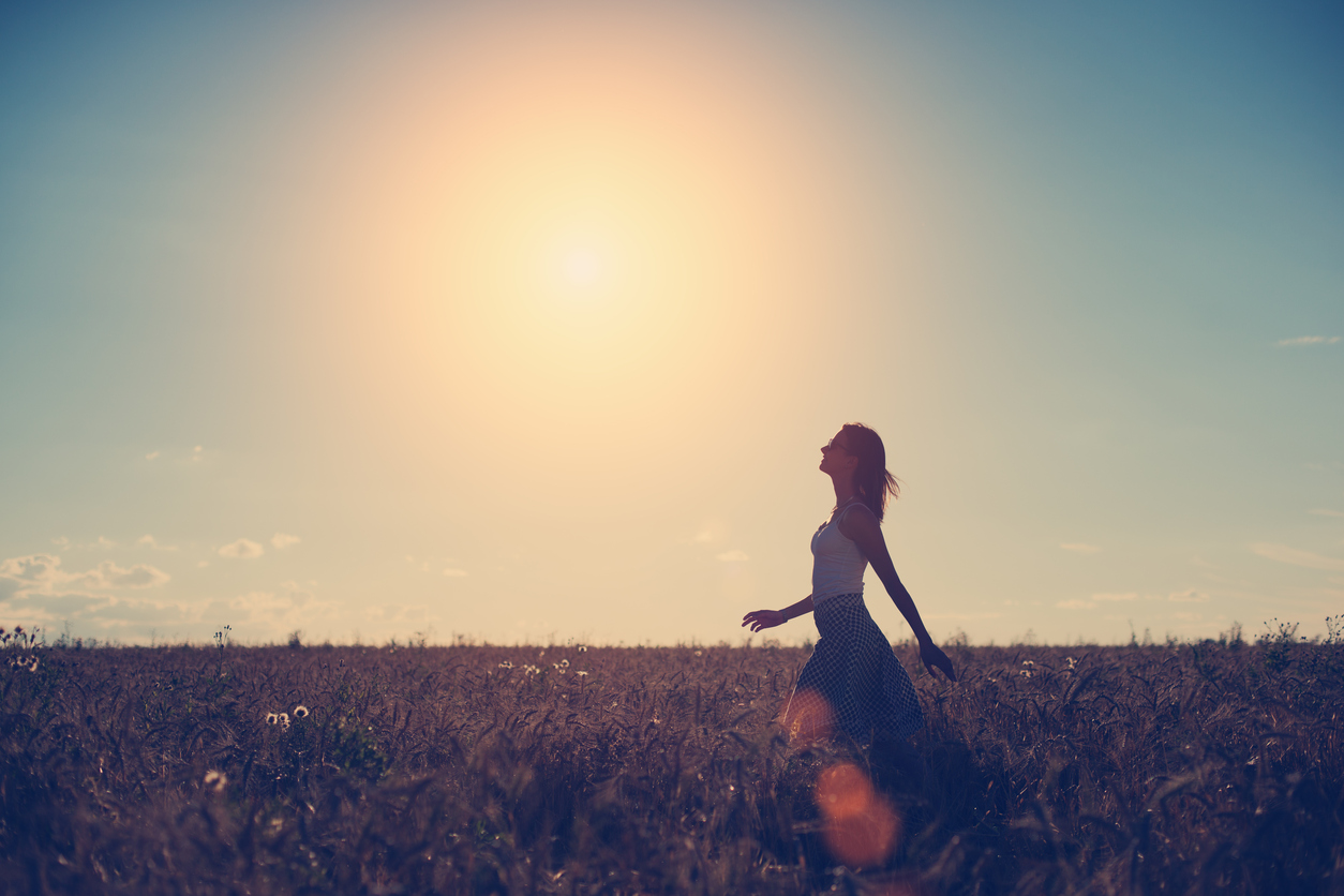 Girl walking in the field in the evening